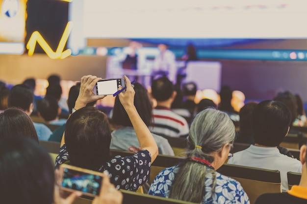 Het publiekshand die van de close-upvrouw slimme mobiele telefoon voor het nemen van foto houden of levend richten stre