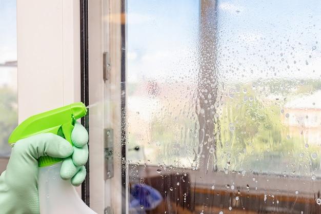 Het raam reinigen met een speciaal sproeisysteem met schuim