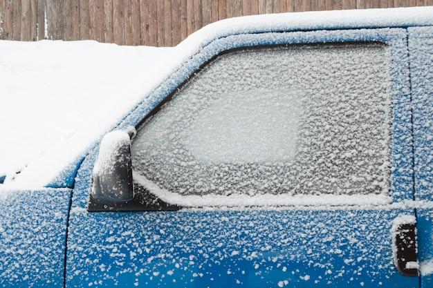Het raam van de autocabine bedekt met sneeuw