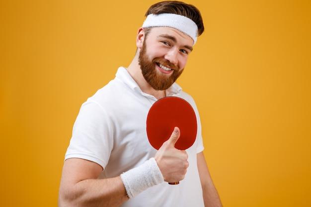 Het racket van de sportmanholding voor pingpong het tonen beduimelt omhoog gebaar.