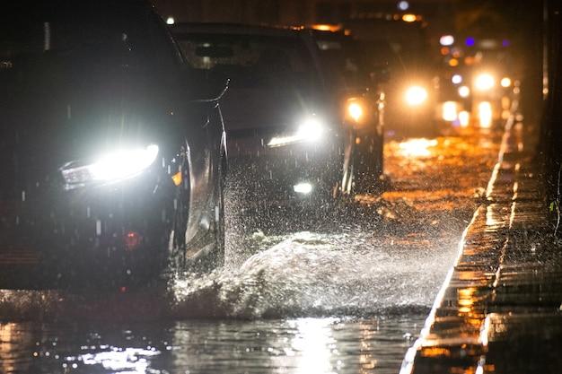 Het regent op de stad op straten met auto's en motorfietsen.
