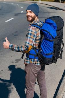 Het reizen voortzetten. knappe jongeman met rugzak die zijn hand uitstrekt en camera door de schouders kijkt met duim omhoog terwijl hij op de weg staat