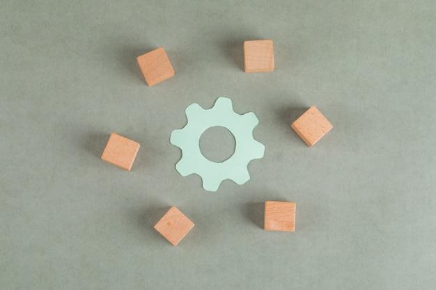 Het reparatieconcept met houten kubussen, montagesymbool op grijze lijstvlakte lag.