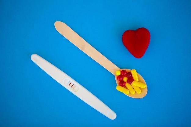 Het resultaat is positief. sluit omhoog van zwangerschapstest en het concept van de anticonceptiepillengeboortenbeperking