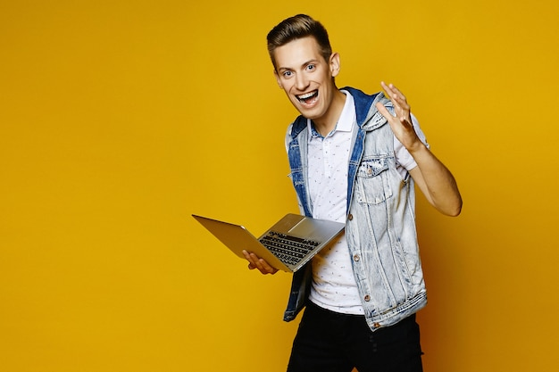 Het richten van positieve kerel met laptop in van hem overhandigt gele achtergrond. jonge hipster met notebook geïsoleerd op gele achtergrond.