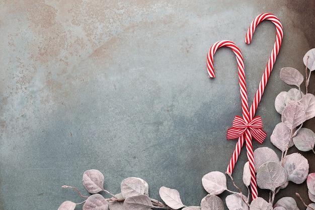 Het riet van het kerstmissuikergoed loog op blauwe achtergrond. plat leggen en bovenaanzicht.