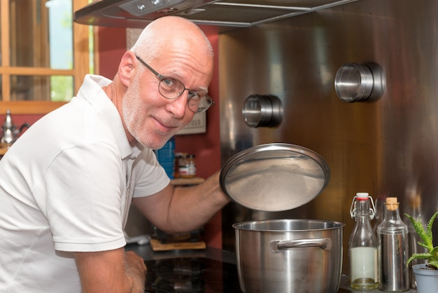 Het rijpe knappe mens koken in huiskeuken