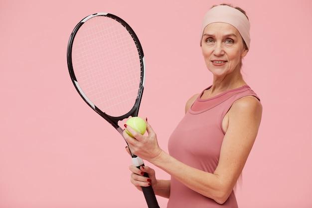 Het rijpe speeltennis van de vrouw tegen roze achtergrond