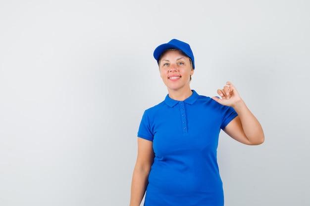 Het rijpe vrouw opheffen dient blauwe t-shirt in en kijkt blij.