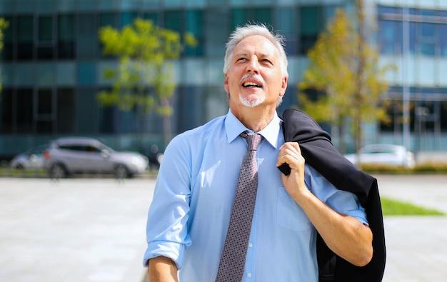 Het rijpe zakenman openlucht lopen in een moderne stad die zijn jasje houden en gelukkig kijken