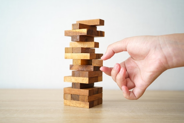 Het risico zal gebeuren. hand van ingenieur die een spel van blokkenhout op houten tafel speelt