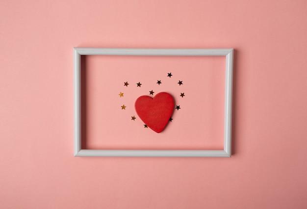Het rode hart met gouden sterren in het witte fotolijstje. valentijnsdag concept. bovenaanzicht, plat gelegd.