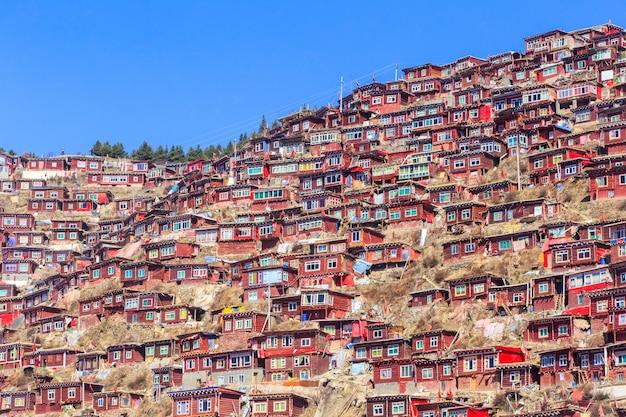 Het rode klooster bij larung-gar (boeddhistische academie) in zonneschijndag en achtergrond is blauwe hemel, sichuan, china