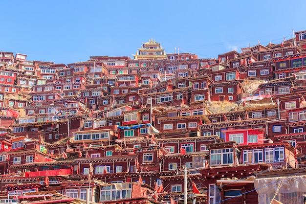 Het rode klooster en het huis in larung-gar (boeddhistische academie) in zonneschijndag en achtergrond zijn blauwe hemel, china