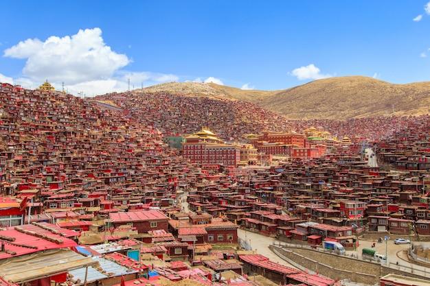 Het rode klooster en het huis in larung-gar (boeddhistische academie) in zonneschijndag en achtergrond zijn blauwe hemel
