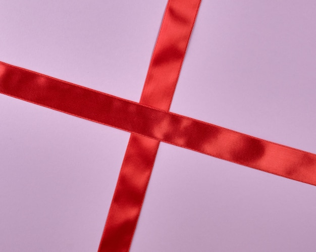Het rode kruis van het satijnlint om op purpere achtergrond te kruisen