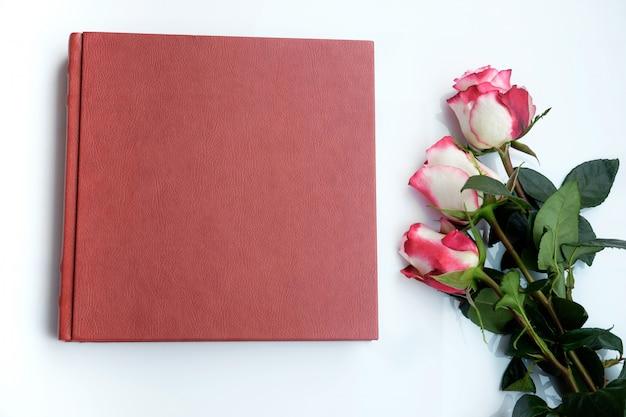 Het rode leer behandelde huwelijksalbum of het huwelijksboek en drie mooie rozen ligt op witte achtergrond