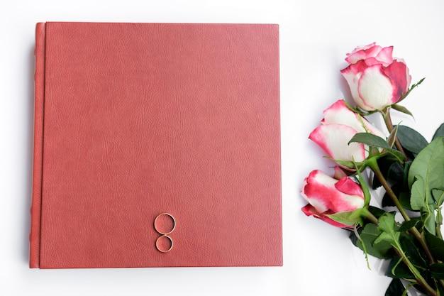 Het rode leer behandelde huwelijksboek of album met twee trouwringen en drie rozen ligt op witte achtergrond.