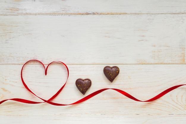 Het rode lint van de giftviering zwaaide in vorm van hart en chocoladesnoepjes op witte houten achtergrond. wenskaart met kopie ruimte voor st valentines day