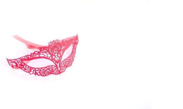 Het rode masker van kantcarnaval op witte achtergrond met exemplaarruimte voor mardi gras, braziliaans, venetiaans carnaval