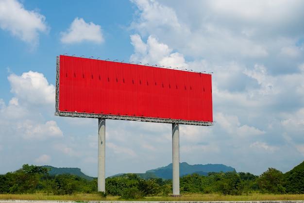 Het rode reclamebord leeg met blauwe lucht