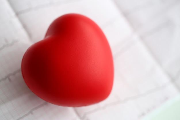 Het rode stuk speelgoed hart ligt op de close-up van het cardiogramgrafiekpapier