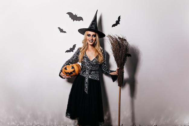 Het romantische blondemeisje stellen met pompoen en vleermuizen. binnen schot van glimlachende jonge vrouw die van halloween carnaval geniet.