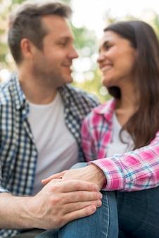 Het romantische gelukkige paar die samen en holding situeren dienen park in