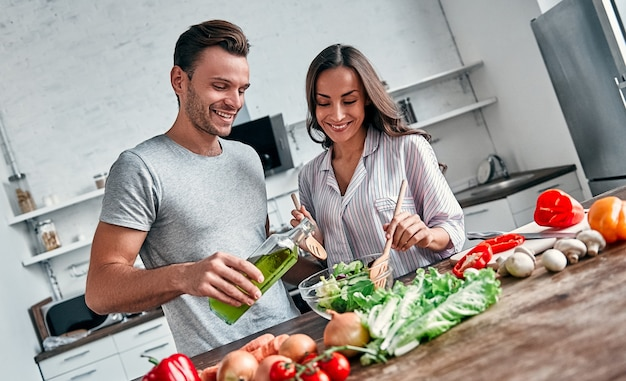 Het romantische paar kookt op keuken. knappe man met een fles olie en aantrekkelijke jonge vrouw hebben samen plezier tijdens het maken van salade. gezond levensstijlconcept.