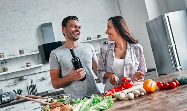 Het romantische paar kookt op keuken. knappe man met een fles wijn en aantrekkelijke jonge vrouw hebben samen plezier tijdens het maken van salade. gezond levensstijlconcept.
