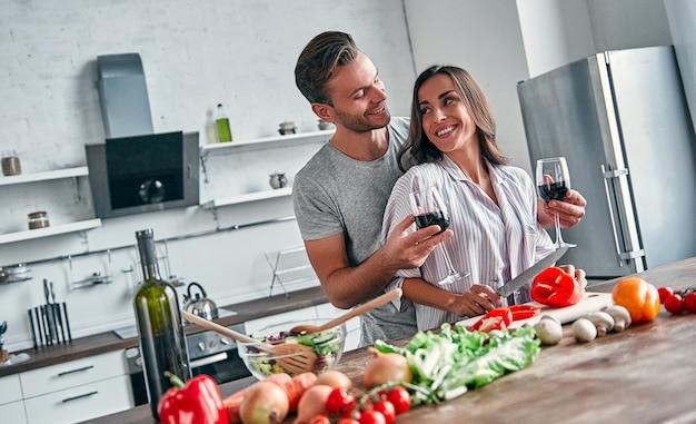 Het romantische paar kookt op keuken. knappe man met glazen wijn en aantrekkelijke jonge vrouw hebben samen plezier tijdens het maken van salade. gezond levensstijlconcept.