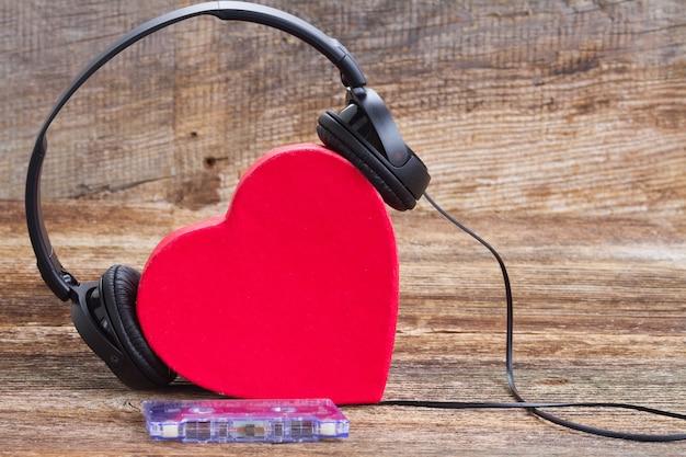 Het romantische rood hart van het muziekconcept met hoofdtelefoons