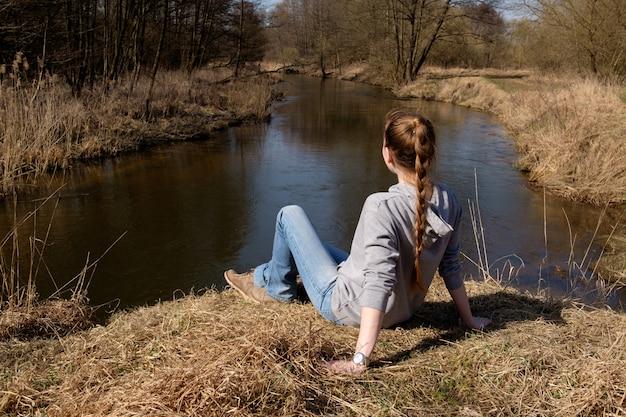 Het roodharige gembermeisje kleedde zich in jeans en grijze hoodiezitting op gras op de bank van bosrivier en ver weg kijkend