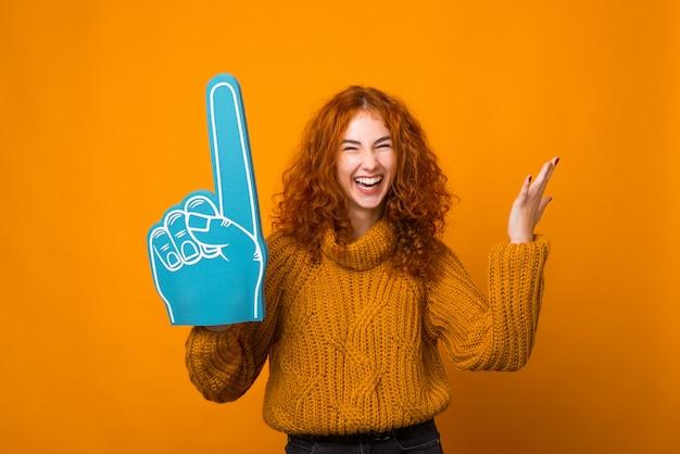 Het roodharige glimlachende meisje houdt een grote ventilatorhandschoen op gele muur.