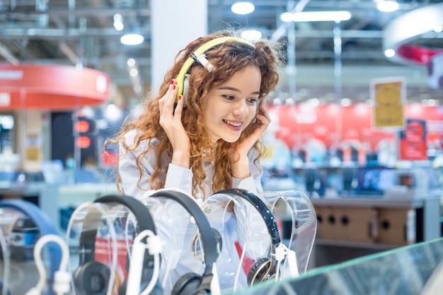 Het roodharige meisje dat zich voor de tribune in de elektronicawinkel bevindt kiest hoofdtelefoons