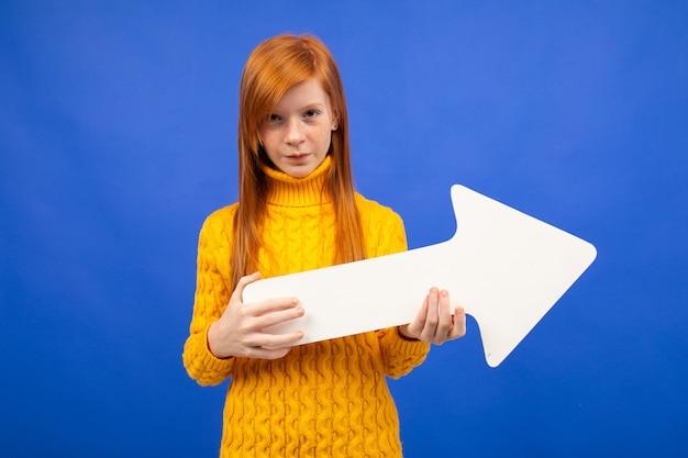 Het roodharige meisje houdt de pijl van de juiste pijl op blauw