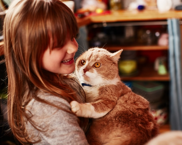 Het roodharige meisje houdt de roodharige kat vast