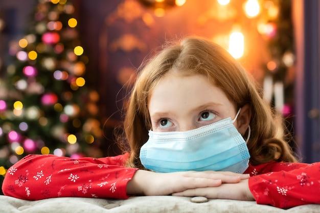 Het roodharige meisje in een medisch masker is verdrietig op kerstavond