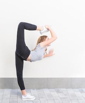 Het roodharige meisje in profiel in ballet stelt haar been boven het hoofd met witte sneakers, zwarte broek en grijs t-shirt op