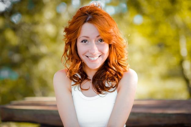 Het roodharige meisje lacht zoet, lacht terug. echte emoties. een mooie vrouw met natuurlijk krullend rood haar en een vrolijke, levendige glimlach.
