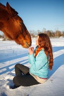 Het roodharige meisje op een sneeuwgebied voedt een appel van handen