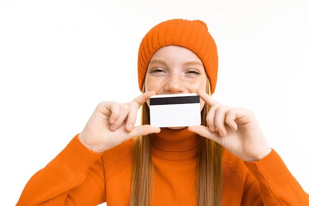 Het roodharige mooie meisje in een oranje hoed houdt een creditcard op een geïsoleerd wit
