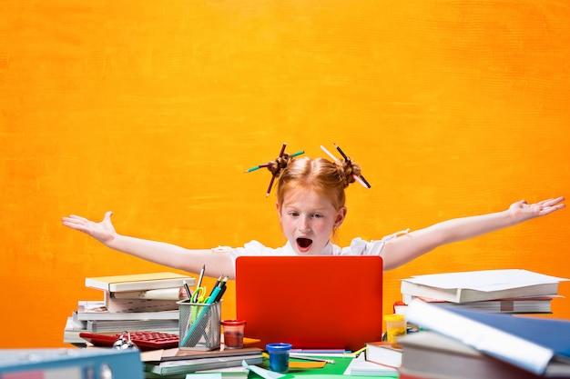 Het roodharige tienermeisje met veel boeken thuis. studio-opname