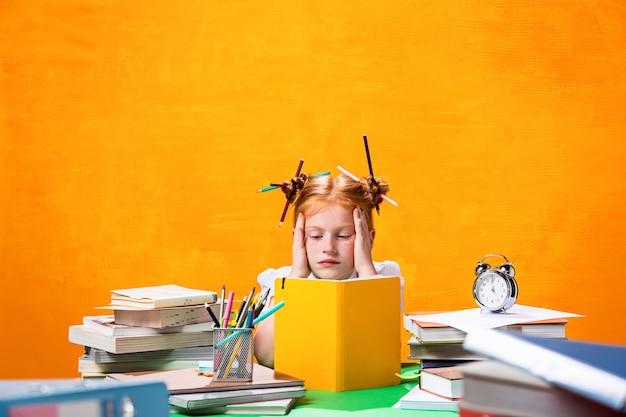 Het roodharige tienermeisje met veel boeken thuis. studio opname
