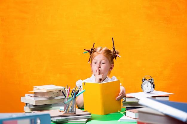 Het roodharige tienermeisje met veel boeken thuis.