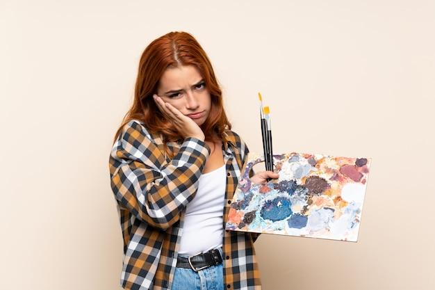 Het roodharigemeisje dat van de tiener een palet ongelukkig en gefrustreerd houdt