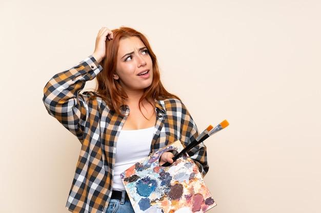Het roodharigemeisje dat van de tiener een palet over geïsoleerde muur houdt die twijfels heeft en met verwarren gezichtsuitdrukking