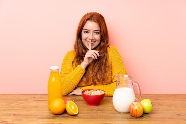 Het roodharigemeisje dat van de tiener ontbijt in een lijst heeft die stiltegebaar doet
