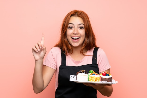 Het roodharigemeisje dat van de tiener veel verschillende minicakes houdt over geïsoleerdt benadrukkend een groot idee