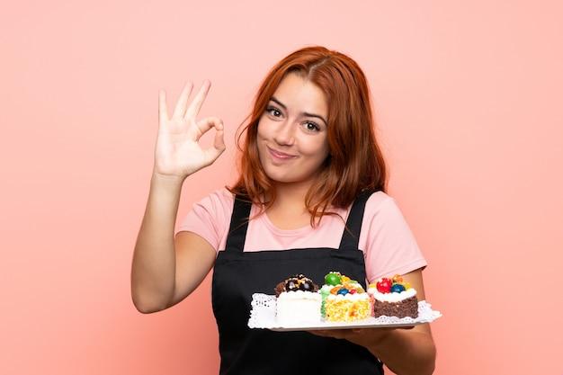 Het roodharigemeisje dat van de tiener veel verschillende minicakes over geïsoleerd roze houdt dat ok teken met vingers toont